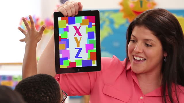 teacher using digital tablet to teach alphabet to kindergarteners - preschool child stock videos & royalty-free footage