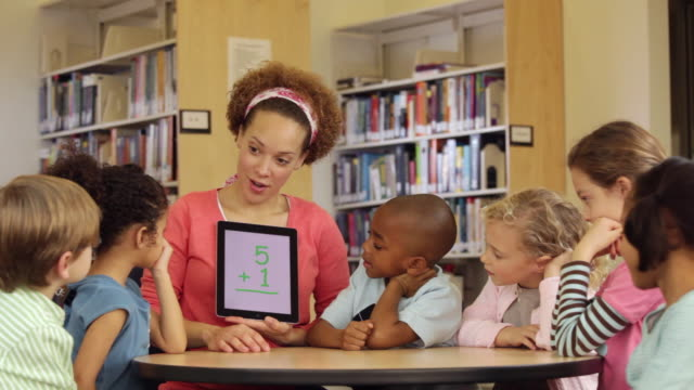 WS Teacher Using Math Flash Cards on Tablet Computer with Students in Library / Richmond, Virginia, USA