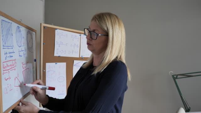 vídeos de stock e filmes b-roll de teacher using white board for geometry and formulas - workshop