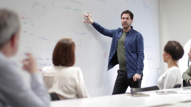 vídeos de stock, filmes e b-roll de teacher using white board in adult education course - aluno mais velho