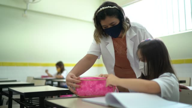 vídeos de stock e filmes b-roll de teacher wearing face mask helping student with disability at school - professora