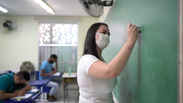 vídeos de stock e filmes b-roll de teacher wearing face mask writing in the blackboard - professora