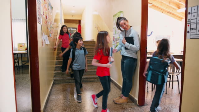 teacher welcoming students in classroom - insegnante video stock e b–roll