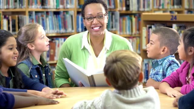 lärare med bok, elementära studenter i biblioteket - 6 7 years bildbanksvideor och videomaterial från bakom kulisserna