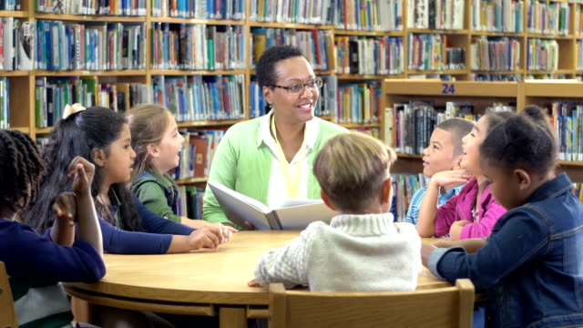 teacher with book, elementary students in library - librarian stock videos & royalty-free footage