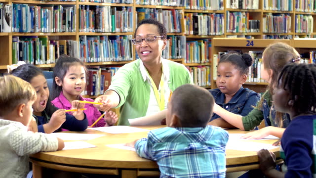 teacher with children in library, handing out paper - 6 7 years stock videos & royalty-free footage