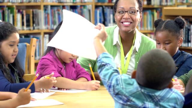 teacher with children in library, writing - passing giving stock videos & royalty-free footage