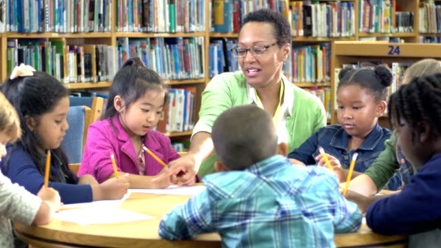 teacher with children in library, writing - giving stock videos & royalty-free footage