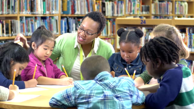 teacher with children in library, writing - 6 7 years stock videos & royalty-free footage