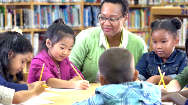 lärare med barn i biblioteket, skrivande - 6 7 years bildbanksvideor och videomaterial från bakom kulisserna