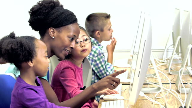 teacher with elementary school students using computers - student stock videos & royalty-free footage