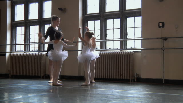 stockvideo's en b-roll-footage met ws slo mo teacher with her students (4-7) in tutus doing arm exercise / chicago, illinois, usa  - gympak
