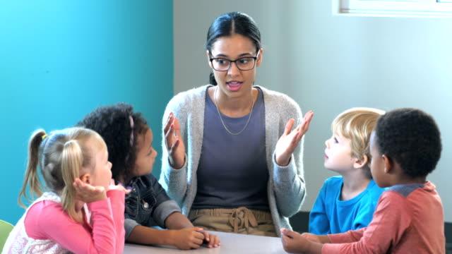 vídeos de stock e filmes b-roll de teacher with preschool students, telling a story - edifício de infantário