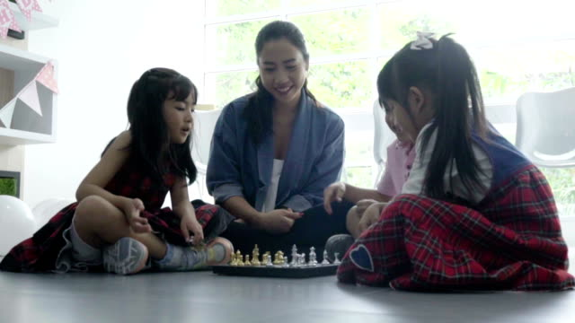 teacher woman with little girl and boy playing chess together - maestra video stock e b–roll