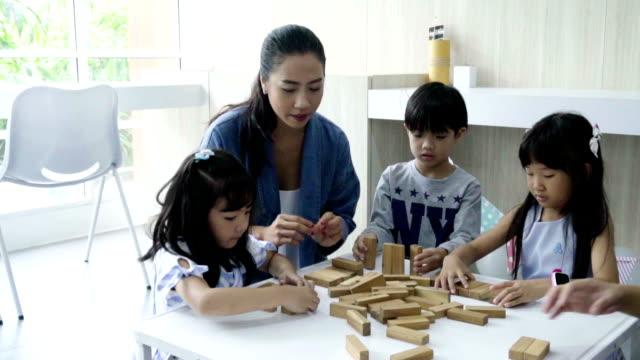 小さな女の子とウッド ブロックを一緒に弾いている少年と教師女性 - 託児施設点の映像素材/bロール