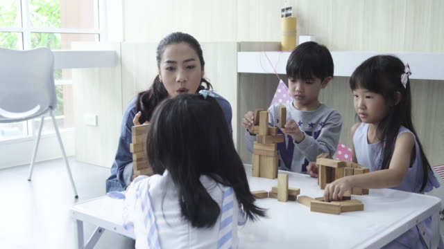 teacher woman with little girl and boy playing wood blocks together - child care stock videos & royalty-free footage