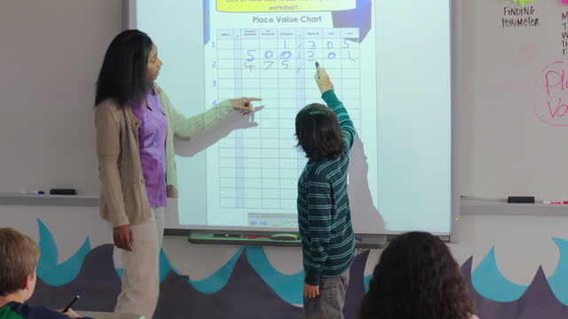 Male student writes on smartboard in front of class, teacher helps him
