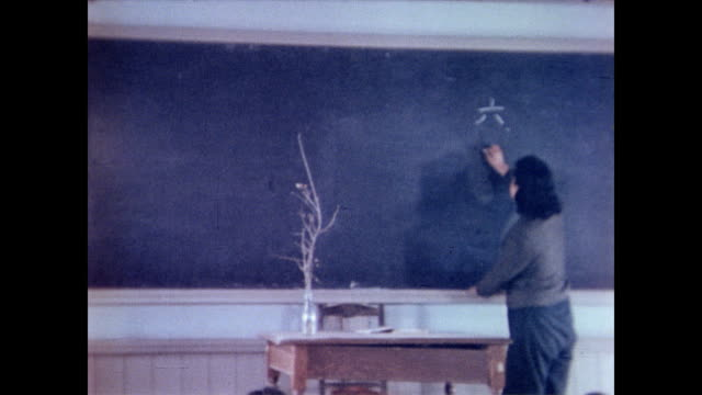 / teacher writes column of characters on the chalk board / children watch attentively nagasaki school in post war japan on january 18 1946 in... - 1946年点の映像素材/bロール