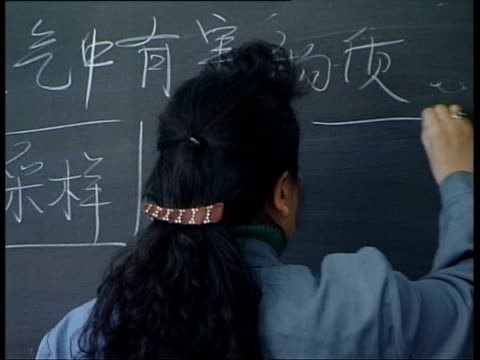 2006 montage cu teacher writing chinese characters on blackboard / ms students in classroom / beijing, china/ audio - svarta tavlan bildbanksvideor och videomaterial från bakom kulisserna