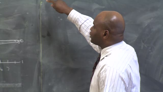 teacher writing on blackboard at st. mel high school on february 25, 2014 in chicago, illinois. - trainer stock videos & royalty-free footage