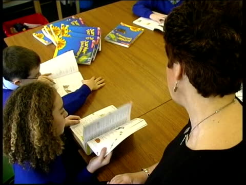 stockvideo's en b-roll-footage met teachers and assistants face redundancy itn teacher talking to child in primary school class lms teacher standing at front of classroom in secondary... - assistent