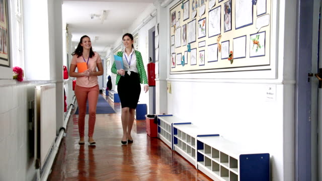 teacher's chatting in the corridor - teacher stock videos and b-roll footage