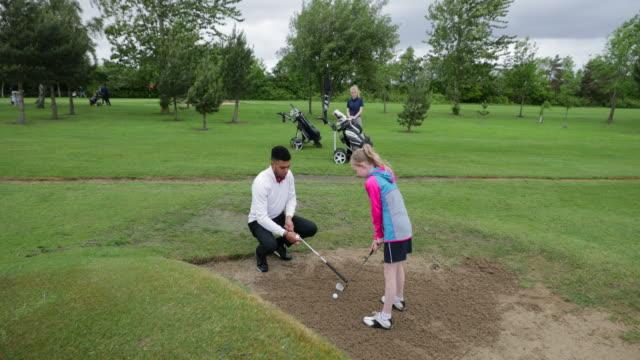 vídeos de stock e filmes b-roll de teaching golf to a young girl - golf
