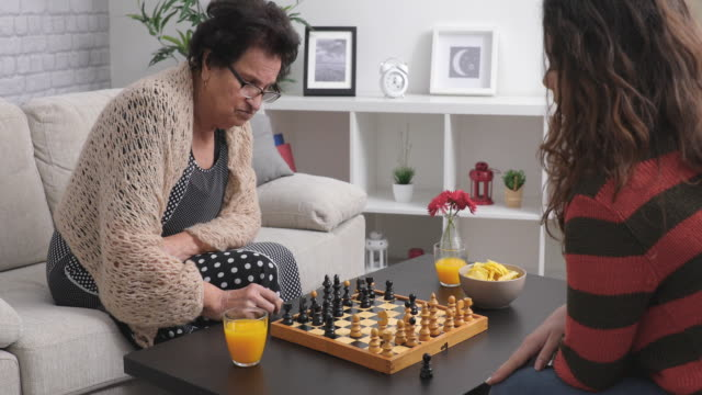 Teaching her granddaughter the basics of chess