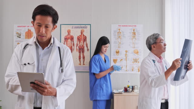 team a doctor working inside the examination room by using the tablet x-ray film and medical devices - medical examination room stock videos & royalty-free footage