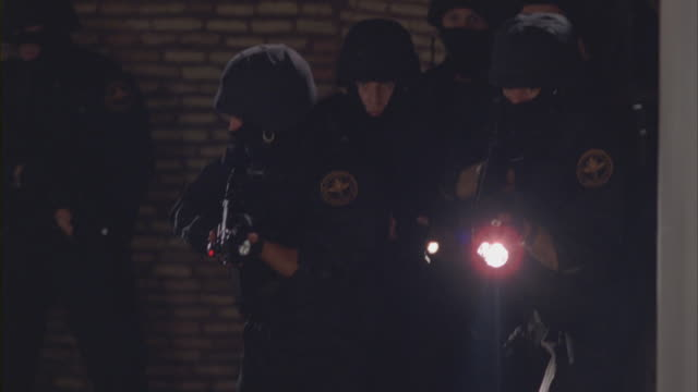 a swat team advances through a building. - position stock-videos und b-roll-filmmaterial