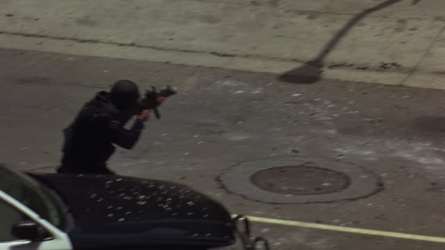A SWAT team and police officers engaging in a gunfire standoff at the scene of a bank robbery.