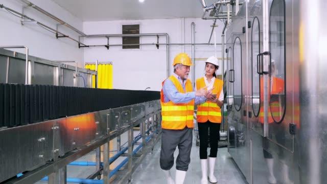 Trabajadores atento equipo examinar una máquina en la fábrica
