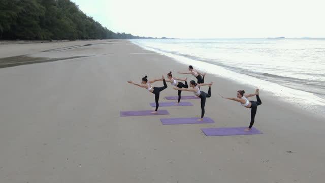 vidéos et rushes de groupe de combat de corps d'équipe faisant le yoga un jour ensoleillé. - équipe sportive