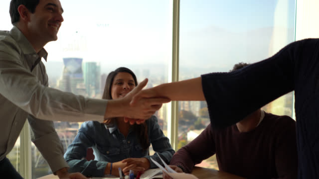 team closing a deal with a handshake all looking very cheerful during a business meeting - assunzione video stock e b–roll