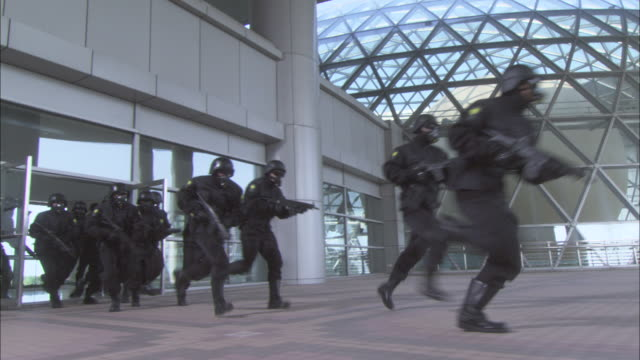 a swat team exits an office building. - aggressione video stock e b–roll