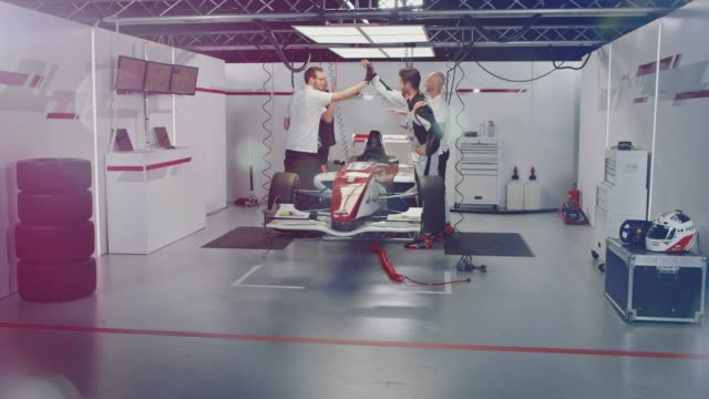 team giving high-fives and cheering at pit stop - sports car stock videos and b-roll footage