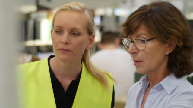 Team leader and her manager discussing in a factory