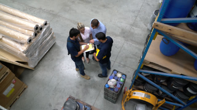 Team meeting at a warehouse between the shelves all looking at a document on clipboard
