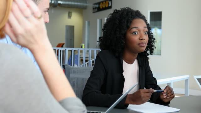 vidéos et rushes de réunion de l'équipe de jeunes gens d'affaires dirigés par une femme entrepreneur - hot desking