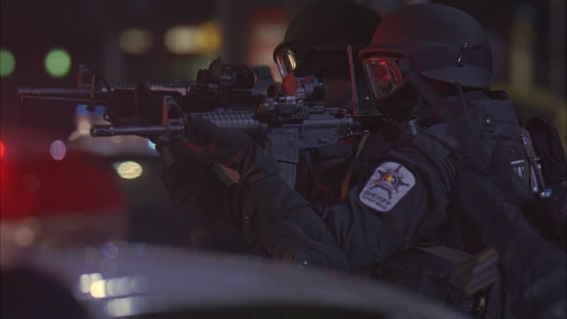 swat team members holding their guns near a vehicle. - shooting a weapon stock videos & royalty-free footage