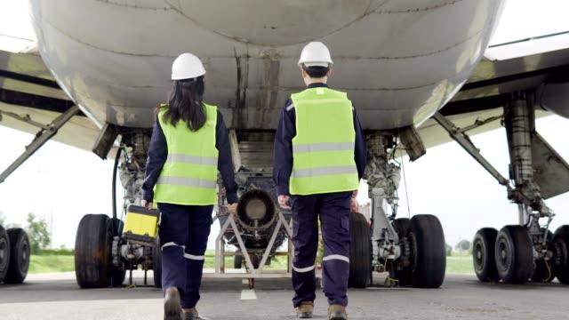 team von flugzeug asiatischen ingenieur wartung reparaturen, reparaturen, modernisierung und renovierung vor dem flugzeug aus dem hangar. - qualitätsprüfer stock-videos und b-roll-filmmaterial