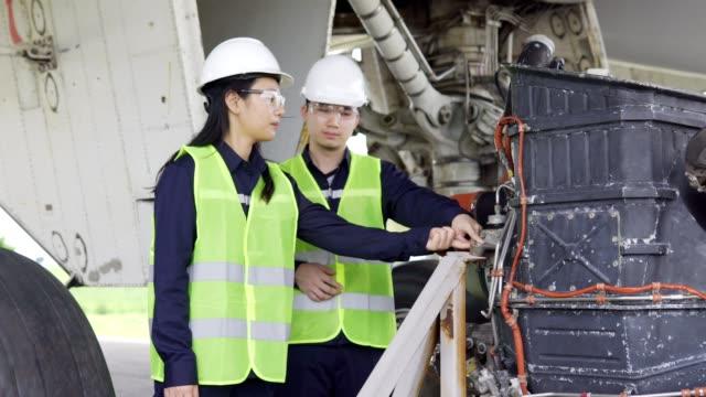 team of airplane asian engineer maintenance repairs,inspect and work on airplane jet engine in hangar. - repairing stock videos & royalty-free footage
