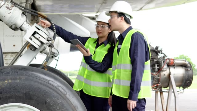 stockvideo's en b-roll-footage met team van vliegtuig aziatische ingenieur onderhoud reparaties, inspecteren en werken aan airplane jet engine in hangar. - technicus