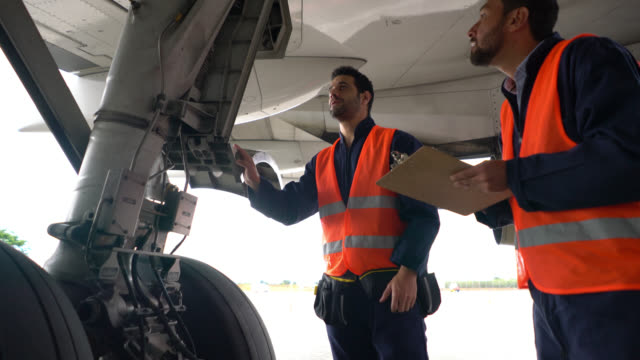 team of airplane mechanics checking the landing gear of an airplane one points at parts and the other one takes notes - aggiustare video stock e b–roll