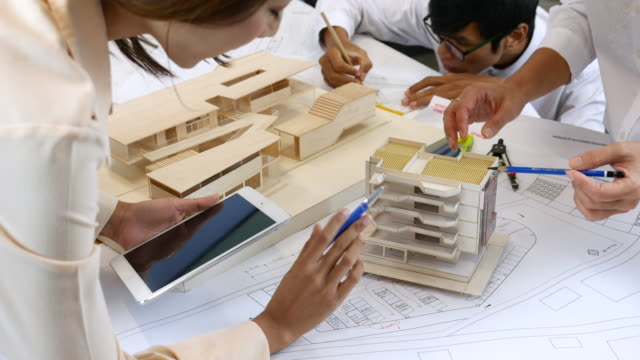 Team of architects brainstorming around the model with artificial model, Architect