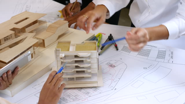 team of architects defining detail of architectural model in office - architectural model stock videos & royalty-free footage