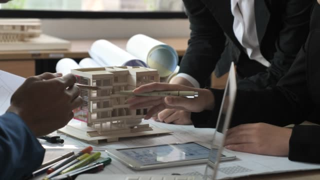 team of architects defining detail of architectural model - architect stock videos & royalty-free footage