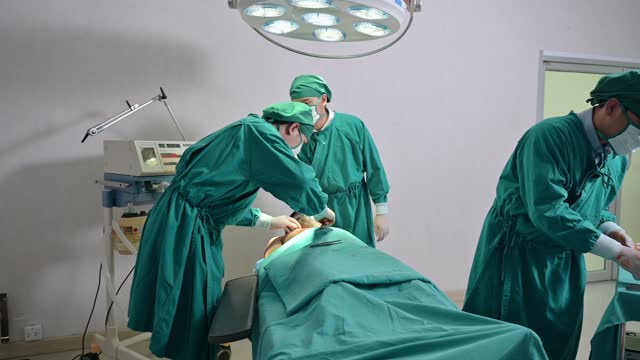 team of asian surgeons in surgical gown performing surgery a seriously injured patient in operating room at hospital - operating gown stock videos & royalty-free footage