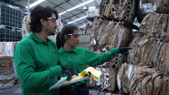 Team of blue collar workers at a recycling center going over the inventory of recycled cartons while looking at documents on clipboard