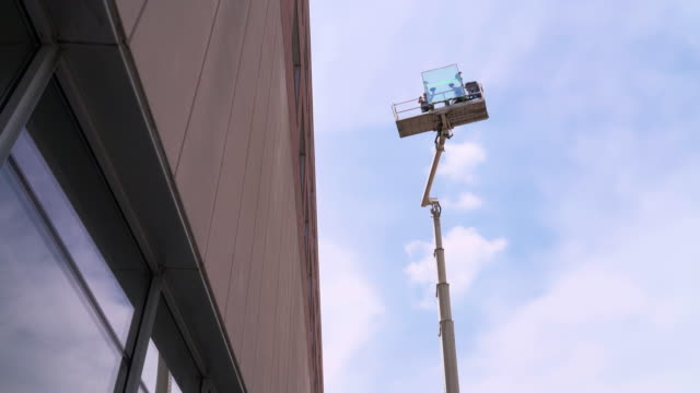 team of blue-collar workers delivering the double-glass to the installation place on the lifting platform. - hoisting stock videos & royalty-free footage